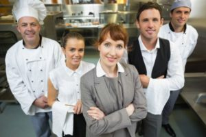 Female hospitality manager with her restaurant team with property compliance responsibility